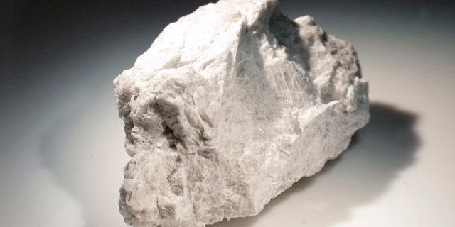 "The ""Genesis Rock,"" a 4.4 billion-year-old anorthosite sample approximately 2 inches in length, brought back by Apollo 15 and used to determine the moon was formed by a giant impact, is lit inside a pressurized nitrogen-filled examination case in the lunar lab at the NASA Johnson Space Center Monday, June 17, 2019, in Houston. (AP Photo/Michael Wyke)"
