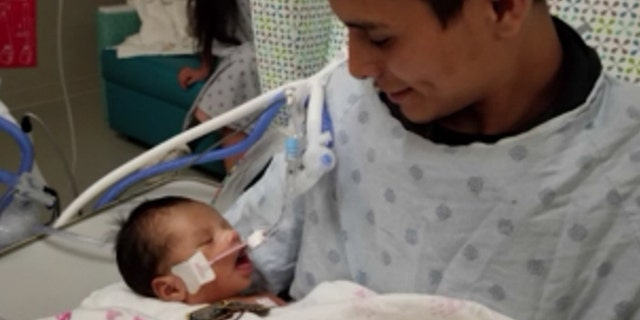 Yovani Lopez holds his son, Yovanny Jadiel Lopez, in the hospital in this photo released by family members.
