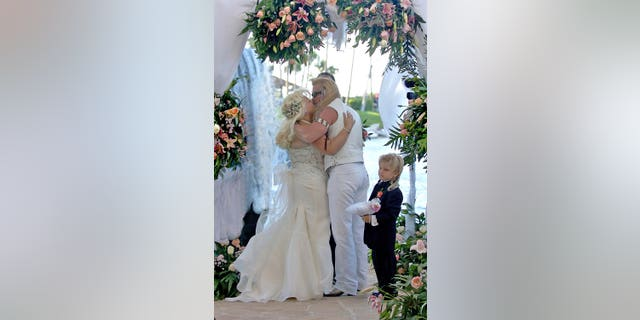 "Beth Chapman wife of Bounty Hunter Duane ""Dog"" Chapman kiss under an archway of roses near the waterfall at the Hilton Waikoloa Village in Waikoloa, on the Big Island of Hawaii, May 20, 2006. The couple married after several dramatic years together and remained together until Beth's death in June 2019."