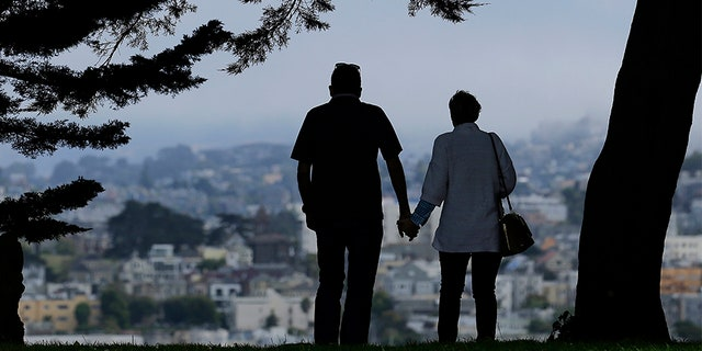 A man and woman walk under trees down a path at Alta Plaza Park in San Francisco. Data from the U.S. Census Bureau shows the median age in the U.S has increased by a year to 38.2 years from 2010 to 2018.