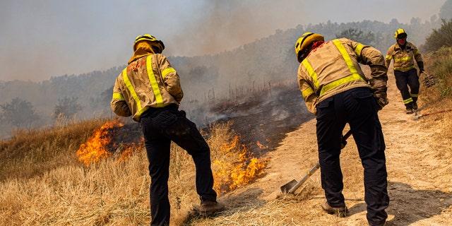 آتش نشانان سعی می کنند یک آتش سوزی را در پالم دپیب، در نزدیکی تارگونا، اسپانیا، پنج شنبه، 27 ژوئن 2019، خاموش کنند. مقامات معتقدند که علت این وقوع، سپرده ای از فروشگاه نامناسب بود (AP Photo / Jordi Borras)