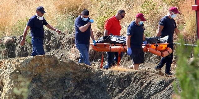 Cyprus police personnel carry a stretcher containing what is believed to be remains of a 6-year-old girl, near the village of Xiliatos, Cyprus, Wednesday, June 12, 2019.