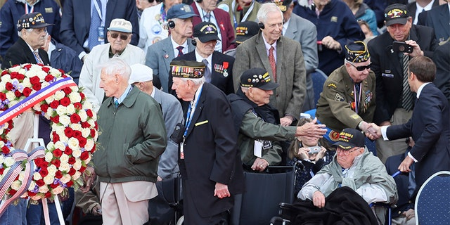 French President Emmanuel Macron, right, greets veterans during a ceremony to mark the 75th anniversary of D-Day at the Normandy American Cemetery in Colleville-sur-Mer, Normandy, France, on Thursday. (AP)