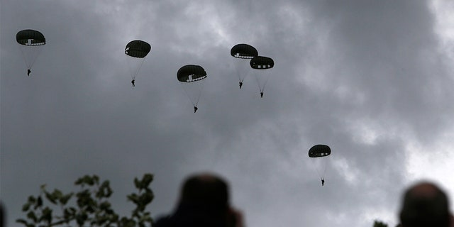 Spectators watch parachutists jumping just as soldiers did 75 years ago for D-Day, Wednesday June 5, 2019 in Carentan, Normandy.