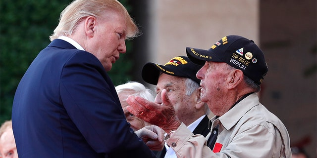 U.S. President Donald Trump talks to a U.S War veteran during a ceremony to mark the 75th anniversary of D-Day at the Normandy American Cemetery in Colleville-sur-Mer, Normandy, France, on Thursday. (AP)