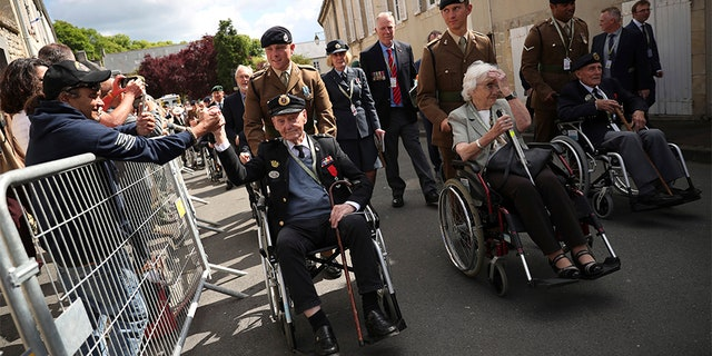 A spectator shakes the hand of a British veteran who is part of a procession leaving the Bayeux Cathedral after a ceremony to mark the 75th anniversary of D-Day in Bayeux, Normandy, on Thursday. (AP)