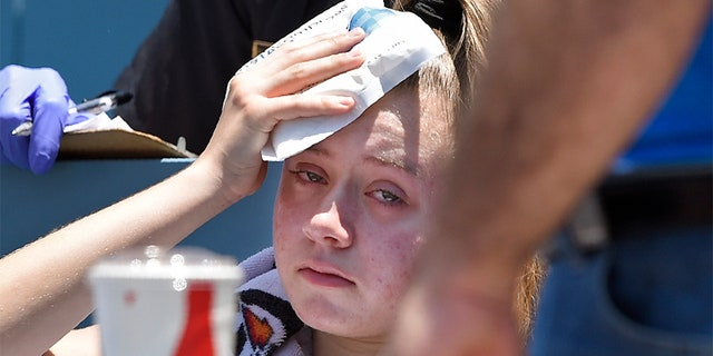A young fan holds ice to her head after being hit with a foul ball hit by Los Angeles Dodgers' Cody Bellinger during the first inning of a baseball game against the Colorado Rockies on Sunday.