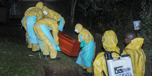 Workers wearing protective clothing bury Agnes Mbambu who died of Ebola, the 50-year-old grandmother of the 5-year-old boy who became Ebola's first cross-border victim, in the village of Karambi, near the border with Congo, in western Uganda Thursday, June 13, 2019. (AP Photo/Ronald Kabuubi)