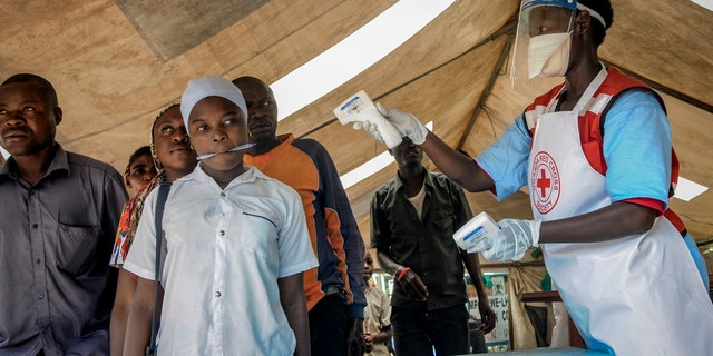 People coming from Congo have their temperature measured to screen for symptoms of Ebola, at the Mpondwe border crossing with Congo, in western Uganda Friday, June 14, 2019. (AP Photo/Ronald Kabuubi)