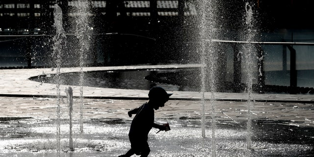 A children plays and cool-off as water sprinkles from a fountain, in Milan, Italy, Monday, June 24, 2019.