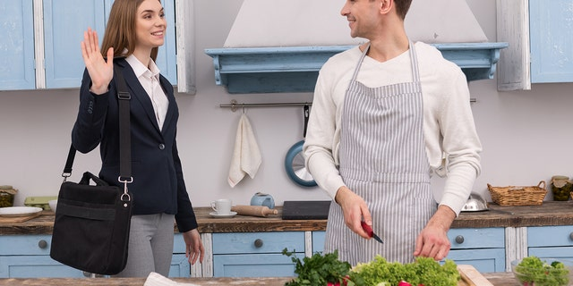 A happy confident woman will work and her husband prepares dinner