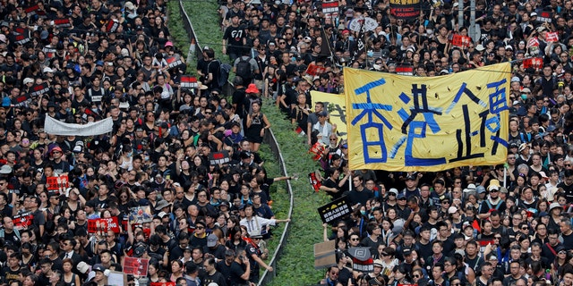 "Tens of thousands of protesters march through the streets with a banner reading ""Hong Kong stand firm"" as they continue to protest an extradition bill, Sunday, June 16, 2019, in Hong Kong."