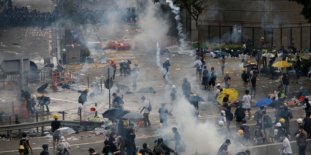 In this file photo taken Wednesday, June 12, 2019, riot police try to disperse protesters with fire tear gas outside the Legislative Council in Hong Kong.