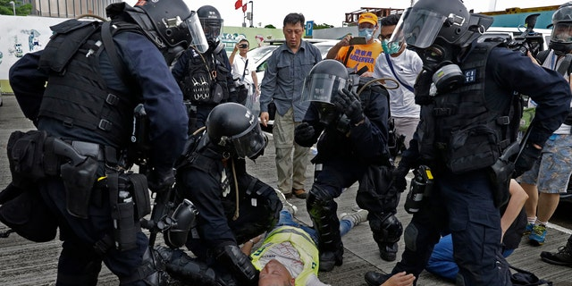 In this file photo taken Wednesday, June 12, 2019, a cameraman lies injured after riot police fire tear gas on protesters outside the Legislative Council in Hong Kong.