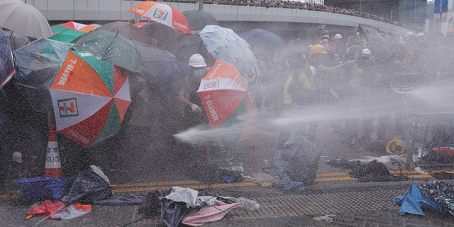Protesters are hit by police water cannon during a demonstration against a proposed extradition bill in Hong Kong, China, using only their umbrellas as protection