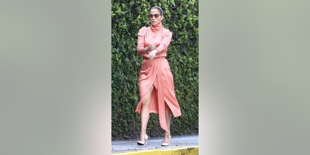 Jennifer Lopez cut a striking figure in a silky wrap dress that showed a lot of leg and her Spanx as she arrived with Alex Rodriguez for his daughter's graduation in Miami.
