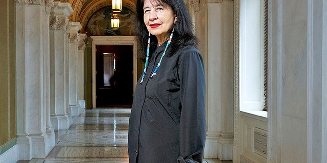 "In this June 6, 2019 photo, Joy Harjo, of the United States, poses inside the Library of Congress, in Washington. Harjo has been named the country's next poet laureate, becoming the first Native American to hold that position. Librarian of Congress Carla Hayden announced Harjo's appointment, saying in a statement Wednesday, June 19 that the poet helped tell an American story of continuity and disruption, ""reckoning and myth-making."" Harjo's one-year term begins this fall. She succeeds Tracy K. Smith, who served two terms."