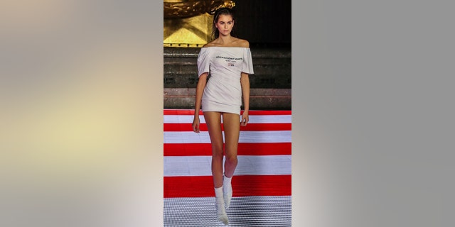 Model Kaia Gerber walks the runway during the Alexander Wang fashion show in New York in a short white dress and boots.