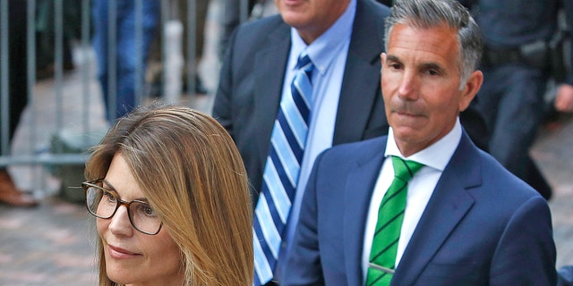 Actress Lori Loughlin, left, leaves as her husband Mossimo Giannulli, right, had their case emboldened in the college admissions scandal by a new judge's order.