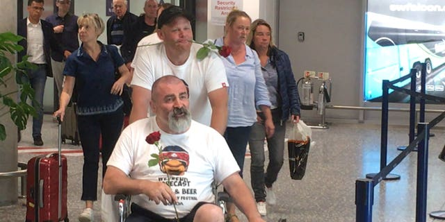 As Mark's friends exited the aircraft, each one approached the waiting Julie and handed her a single rose.