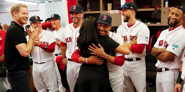 Meghan, Duchess of Sussex embraces Boston Red Sox player Mookie Betts.