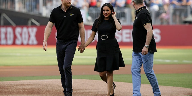 Britain's Prince Harry, left, and Meghan, Duchess of Sussex, walk off the field.