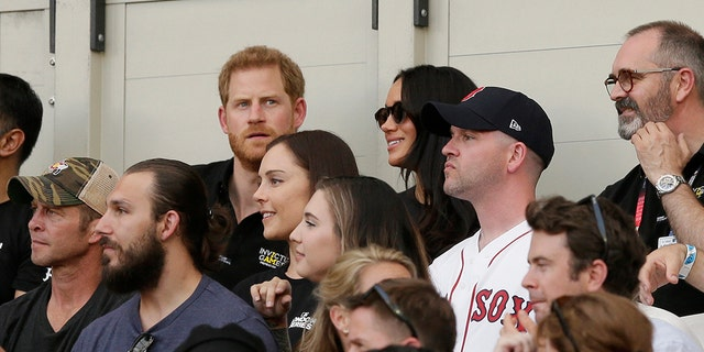 Britain's Prince Harry, top left, and Meghan, Duchess of Sussex, watch during the first inning of a baseball game.