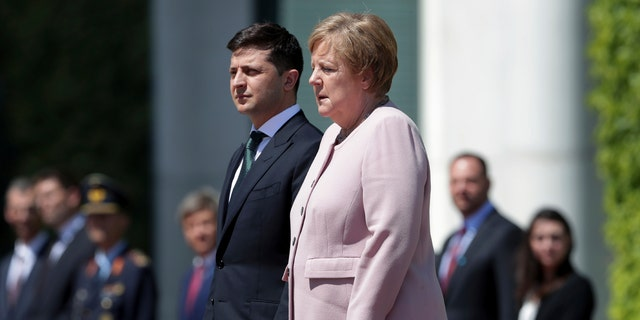 German Chancellor Angela Merkel, right, trembles strong as she and Ukraine's President Volodymyr Zelenskiy, left, attend the national anthems as part of a military welcome ceremony in Berlin, Germany. AP Photo/Michael Sohn