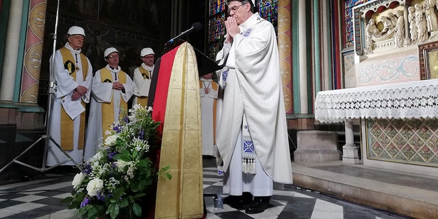 The Archbishop of Paris Michel Aupetit leads the first mass in a side chapel two months to the day after a devastating fire engulfed the Notre-Dame de Paris cathedral, in Paris, France