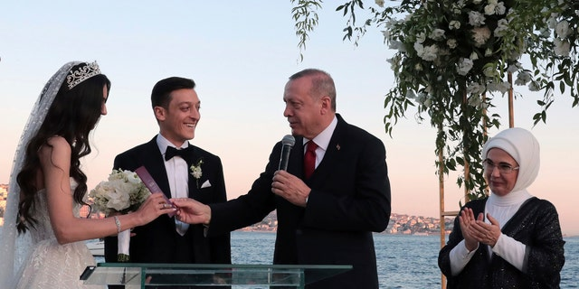 Turkey's President Recep Tayyip Erdogan speaks to Turkish-German soccer player Mesut Ozil and his wife Amine Gulse during a wedding ceremony over the Bosporus in Istanbul, Friday, June 7, 2019. (Presidential Press Service via AP, Pool)