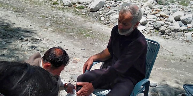 In this photo provided by Gilgit Baltistan regional police department, a mountaineer receives initial treatment following his rescue, at a helipad in the town of Imit, Ghizer district of Gilgit Balistan region, Pakistan, Tuesday, Jun 18, 2019.