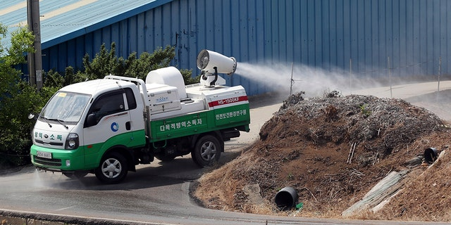 In this June 3, 2019, photo, health officials spray disinfectant solution as a precaution against African swine fever near a pig farm in Incheon, South Korea.
