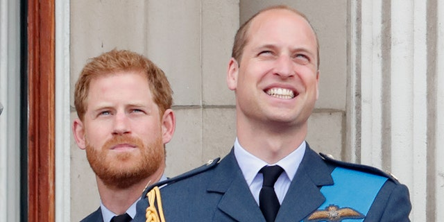 Prince Harry (left) and his older brother Prince William watch a flypast to mark the centenary of the Royal Air Force from the balcony of Buckingham Palace on July 10, 2018, in London, England.