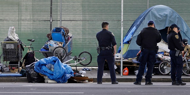 San Francisco police officers wait while homeless people collect their belongings in San Francisco.