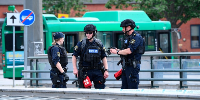 Police officers attend the scene after police shot and wounded a man at Malmo central station, Sweden, Monday June 10, 2019.