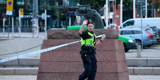 A police officer cordons off an area at the scene where police shot and wounded a man at Malmo central station, Sweden.