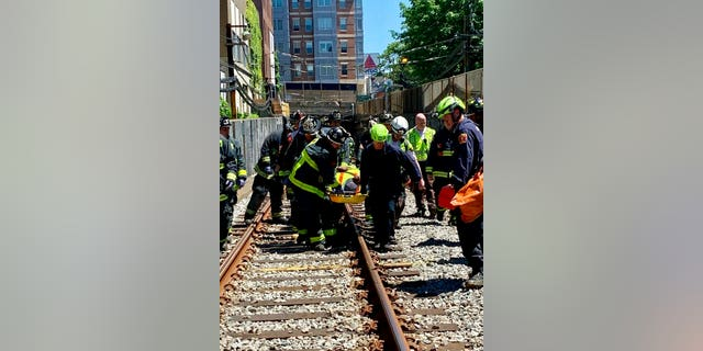This photo provided by the Boston Fire Department, Firefighters and EMT personnel carry an injured person after a train car derailed in Boston on Saturday. Officials with the Massachusetts Bay Transportation Authority said the accident occurred at about 11 a.m. Saturday when a Green Line subway car derailed in a tunnel near Kenmore Square. Officials said several people were injured but none of the injuries are life-threatening. The cause of the derailment is under investigation. (Boston Fire Dept. via AP)