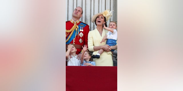 Prince William, Catherine, Duchess of Cambridge, Prince George, Princess Charlotte and Prince Louis, watch as the Royal Air Force Aerobatic Team Red Arrows performs
