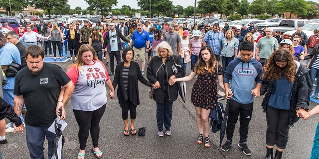 The community prayed together on Saturday during the vigil at Strawbridge Marketplace for the victims of the shooting. (Daniel Sangjib Min/Richmond Times-Dispatch via AP)