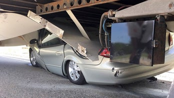 Driver suffers minor injuries after car gets wedged under truck