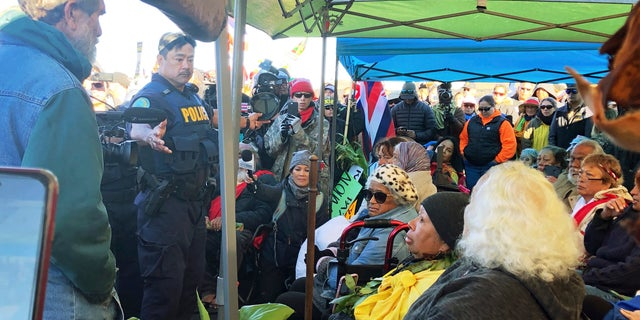 Officers from the Hawaii Department of Land and Natural Resources prepare to arrest protesters, many of them elderly, who are blocking a road to prevent construction of a giant telescope on a mountain that some Native Hawaiians consider sacred, on Mauna Kea on the Big Island of Hawaii, July 17, 2019. (Cindy Ellen Russell/Honolulu Star-Advertiser via AP)
