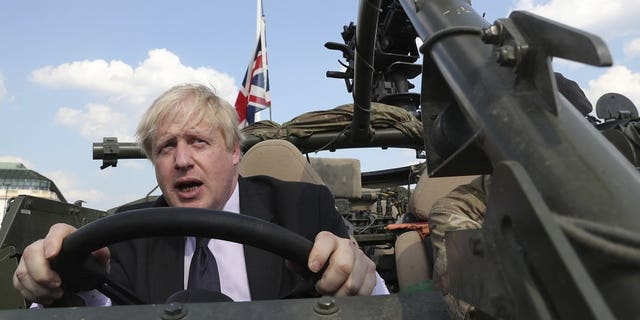 In this Thursday, June 21, 2018 file photo Britain's Foreign Secretary Boris Johnson talks to a British armed forces serviceman based in Orzysz, in northeastern Poland, during a ceremony at the Tomb of the Unknown Soldier and following talks on security with his Polish counterpart Jacek Czaputowicz in Warsaw, Poland. Boris Johnson aspires to be a modern-day Winston Churchill. Critics fear he's a British Donald Trump.