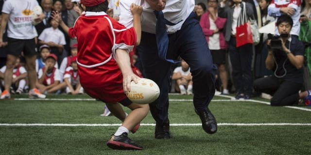 In this Oct. 15, 2015 file photo, Boris Johnson takes part in a Street Rugby tournament in a Tokyo street, wiping out a Japanese school boy in the process