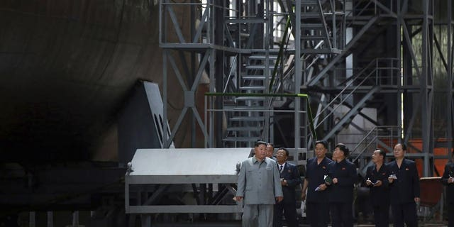 In this undated photo provided on Tuesday, July 23, 2019, by the North Korean government, North Korean leader Kim Jong Un, left, inspects a newly built submarine to be deployed soon, at an unknown location in North Korea.