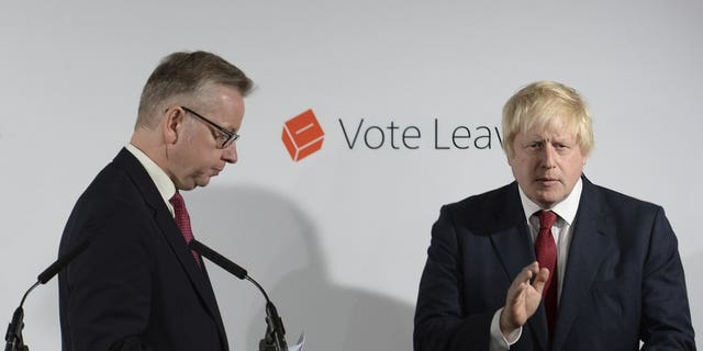 FILE - In this Friday June 24, 2016 file photo Vote Leave campaigners Michael Gove, left, leaves the lectern as Boris Johnson applauds at a press conference at Vote Leave headquarters in London.
