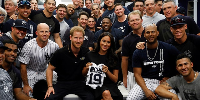 Britain's Prince Harry and Meghan, Duchess of Sussex pose for a picture with players of the New York Yankees before a match against the Boston Red Sox in London, on June 29, 2019.