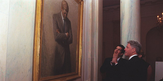 President Clinton takes John F. Kennedy Jr. and Carolyn Bessette for a White House tour where they stop and admire President Kennedy's portrait.