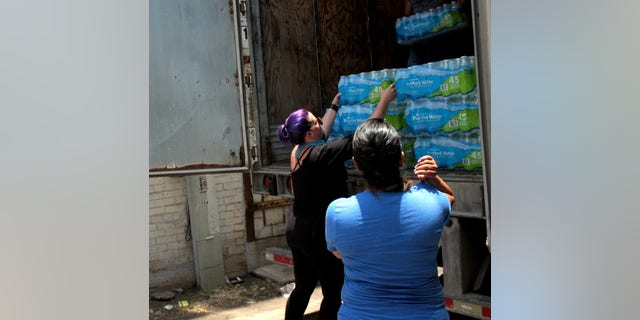 Destiny Herndon-De La Rosa, New Wave Feminists, unloads water at respite center in McAllen, Texas.