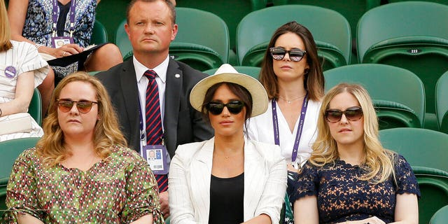 FILE: Meghan, Duchess of Sussex, center, on Court Number One to watch United States' Serena Williams play Slovenia's Kaja Juvan in a singles match during day four of the Wimbledon Tennis Championships in London.