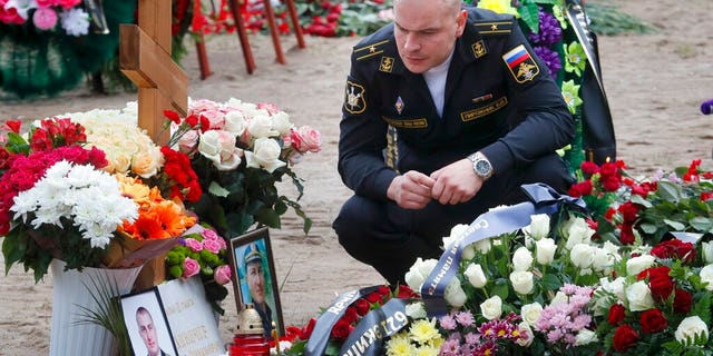 A Russian navy officer pays his last respect at the grave of Captain 3rd rank Vladimir Sukhinichev, one of the 14 crew members who died